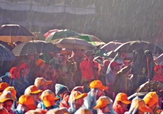 昨天在廣西武鳴縣標營路「三月三」歌圩開幕式現場,人們紛紛拿出雨具躲避突如其來的降雨。當日10時,中央氣象台發布強對流天氣預報,預計2日14時至3日14時,貴州西南部、廣西東部、廣東大部等地的部分地區將有短時強降水天氣。 / (新華社)