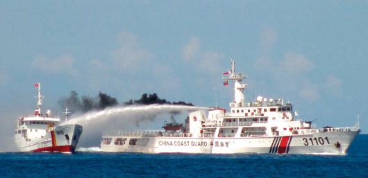 越南海巡署八日公布的照片,顯示一艘大陸海警船(右)三日在西沙群島海域向越南海巡船(左)發射水砲。 / 路透