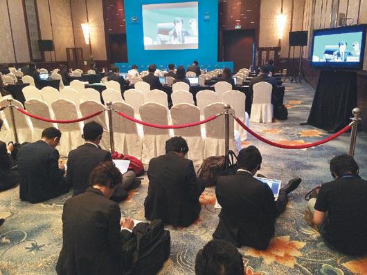 APEC貿易部長會議昨天開幕,主辦方把部分媒體隔離在旁聽區站著採訪。多數記者只好拿出筆電,坐在地上工作,對照前方近百個空位子,十分諷刺。 / 特派記者陳言喬/攝影