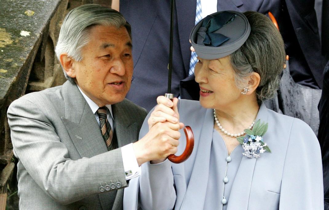 日皇明仁及皇后美智子在訪問英國牛津大學三一學院時,共撐一把傘。法新社