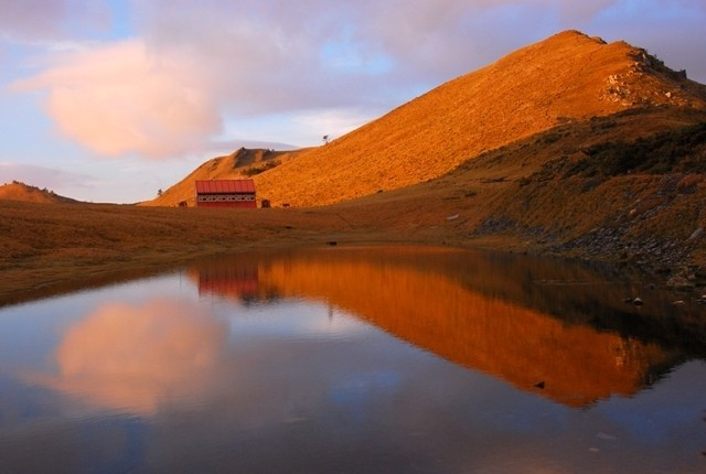 南二段大水窟山屋的清晨,朝陽灑在南大水窟山上,和山屋一起倒映在大水窟水池。