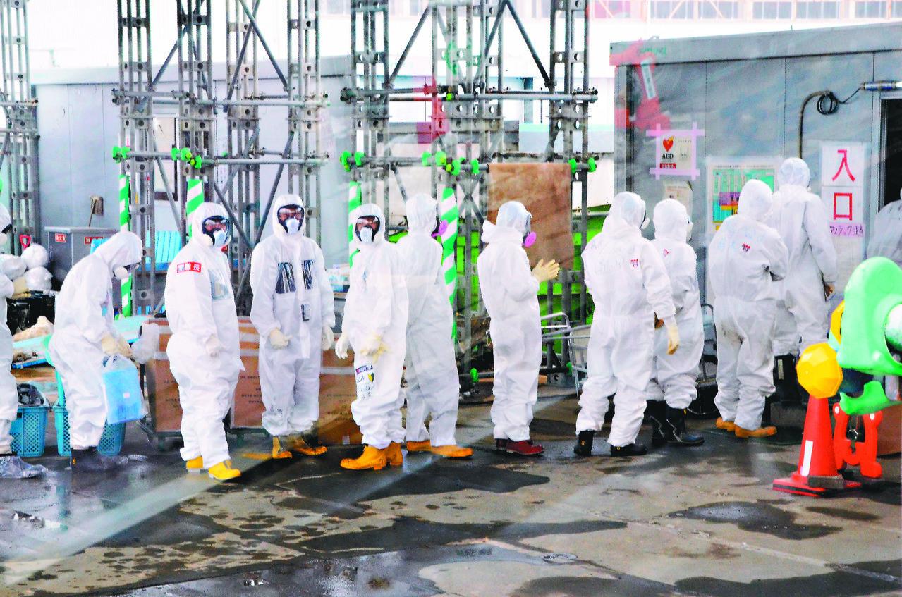 穿著全套防輻射裝備的福島一廠工作人員。聯合報系圖庫