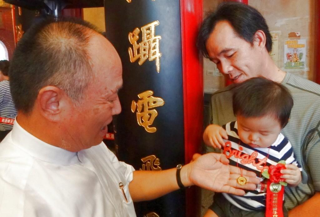 董事長何達煌(左)把穿有紅絲線的貫錢掛在幼童身上。聯合報系資料照/記者陳永順攝影